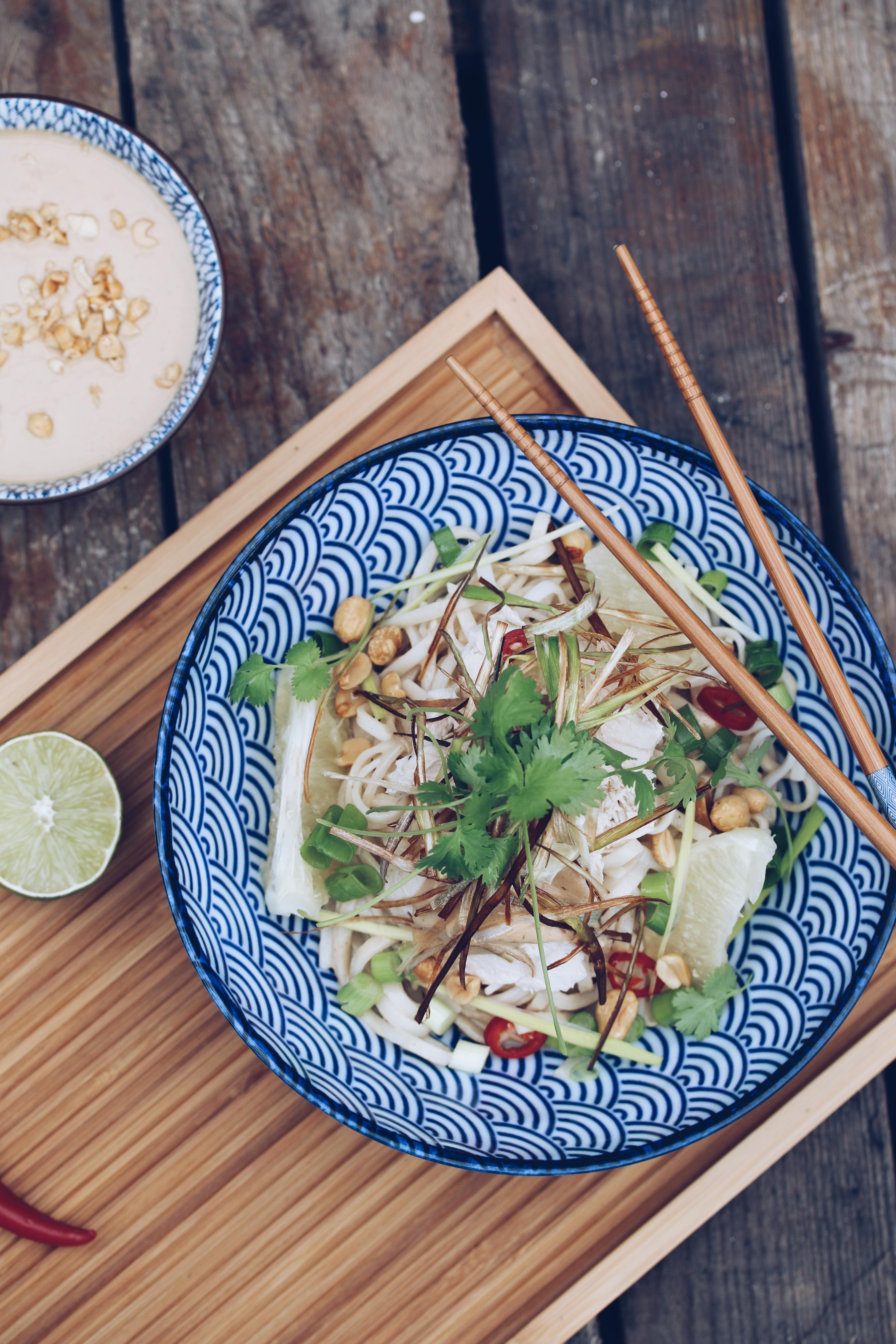 Thaise noedelsalade met gepocheerde kip , pindadressing en pompelmoes.