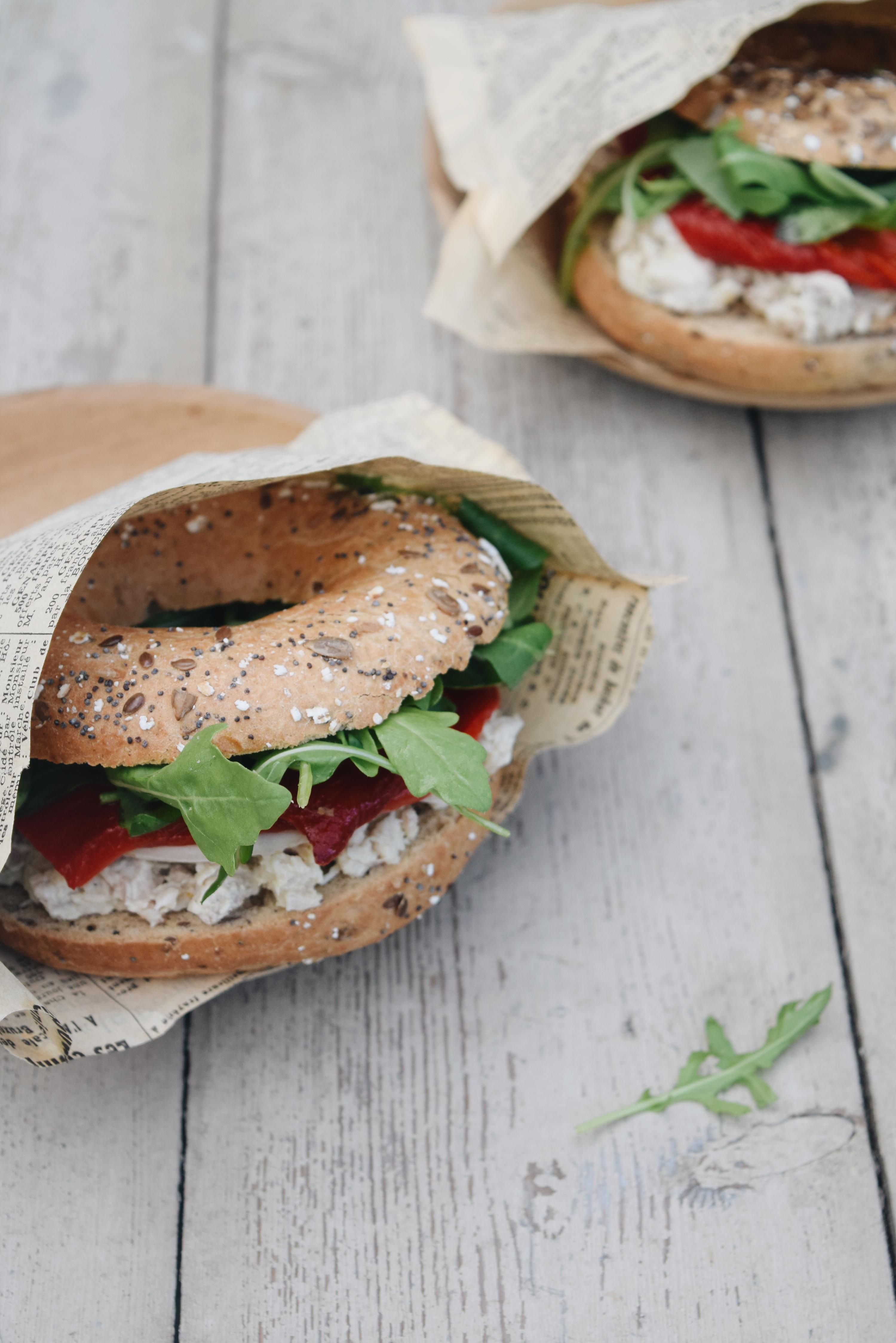Bagel met verse kip salade, geroosterde zoete paprika en rucola